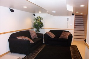 Basement with black couches and view of stairs