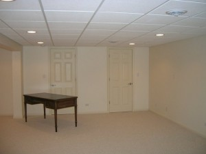 Empty white basement with brown desk