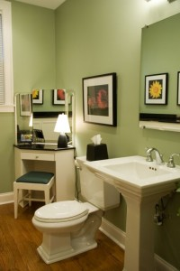 View of green bathroom with white toilet and sink