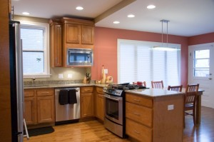 View of a coral colored kitchen with wooden cabinets